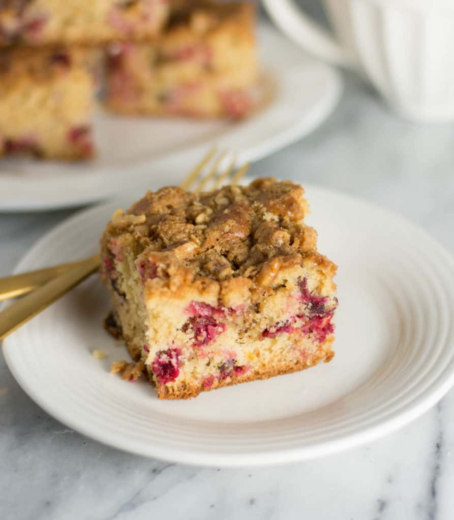 slice of cranberry coffee cake on a plate with two forks next to it
