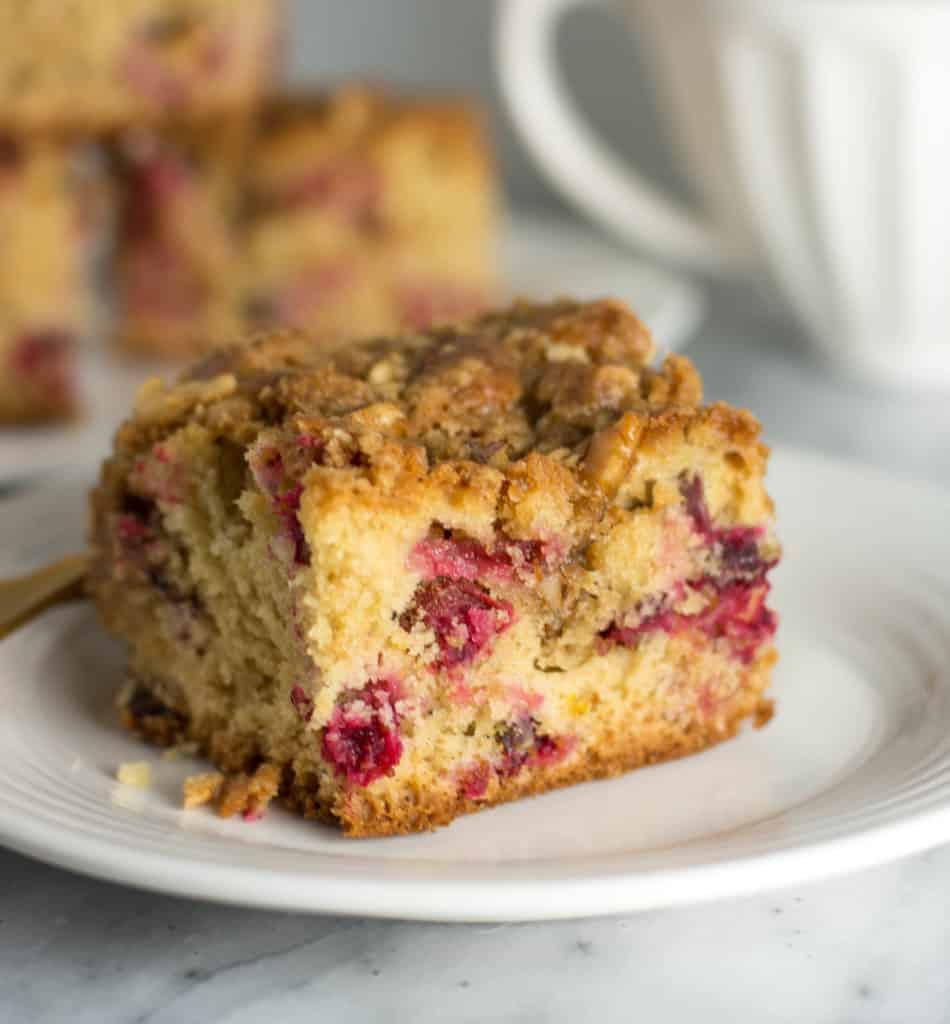 slice of cardamom cranberry coffee cake on a plate with coffee mugs in the background