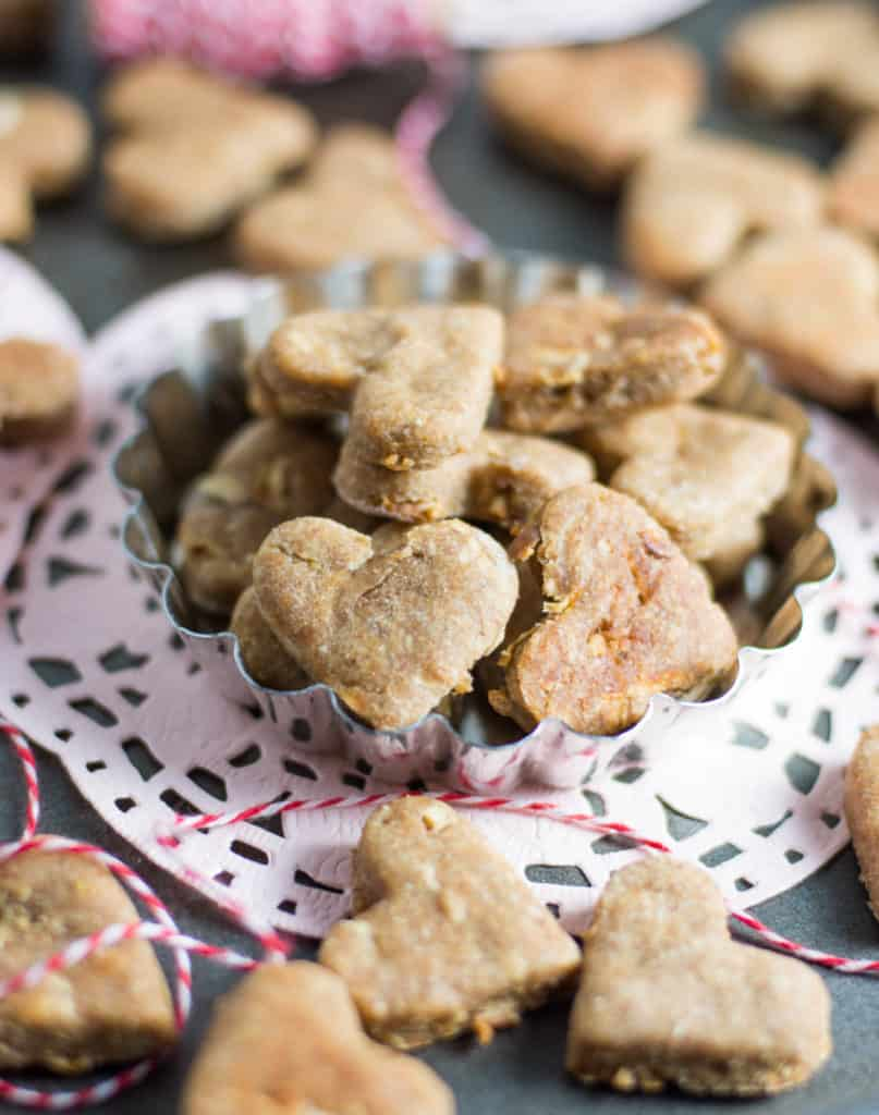 apple peanut butter dog treats in a tart pan sitting on a pink doily
