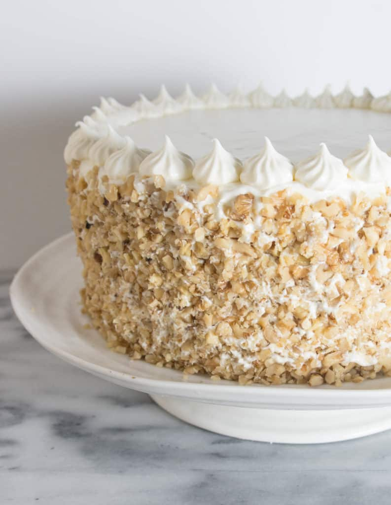 frosted carrot cake cheesecake cake covered in walnuts sitting on a cake stand
