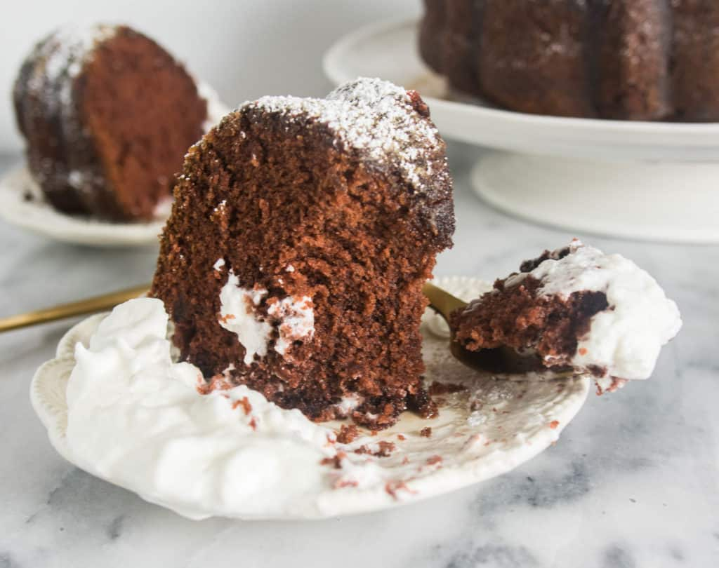 slice of kahlua bundt cake with whipped cream on a plate with a fork taking a bite out of it