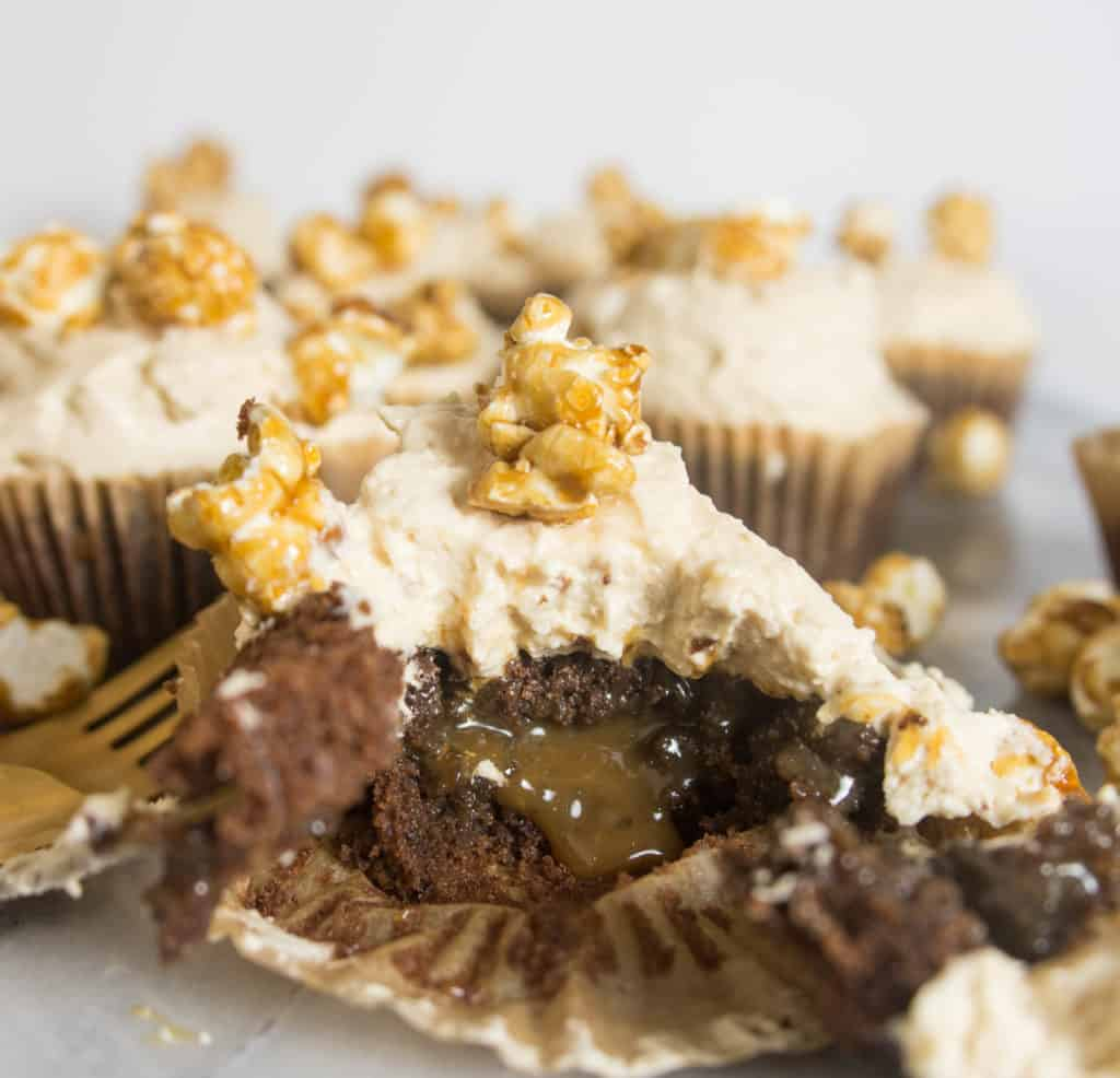 chocolate caramel corn cupcake split open to show the caramel filling