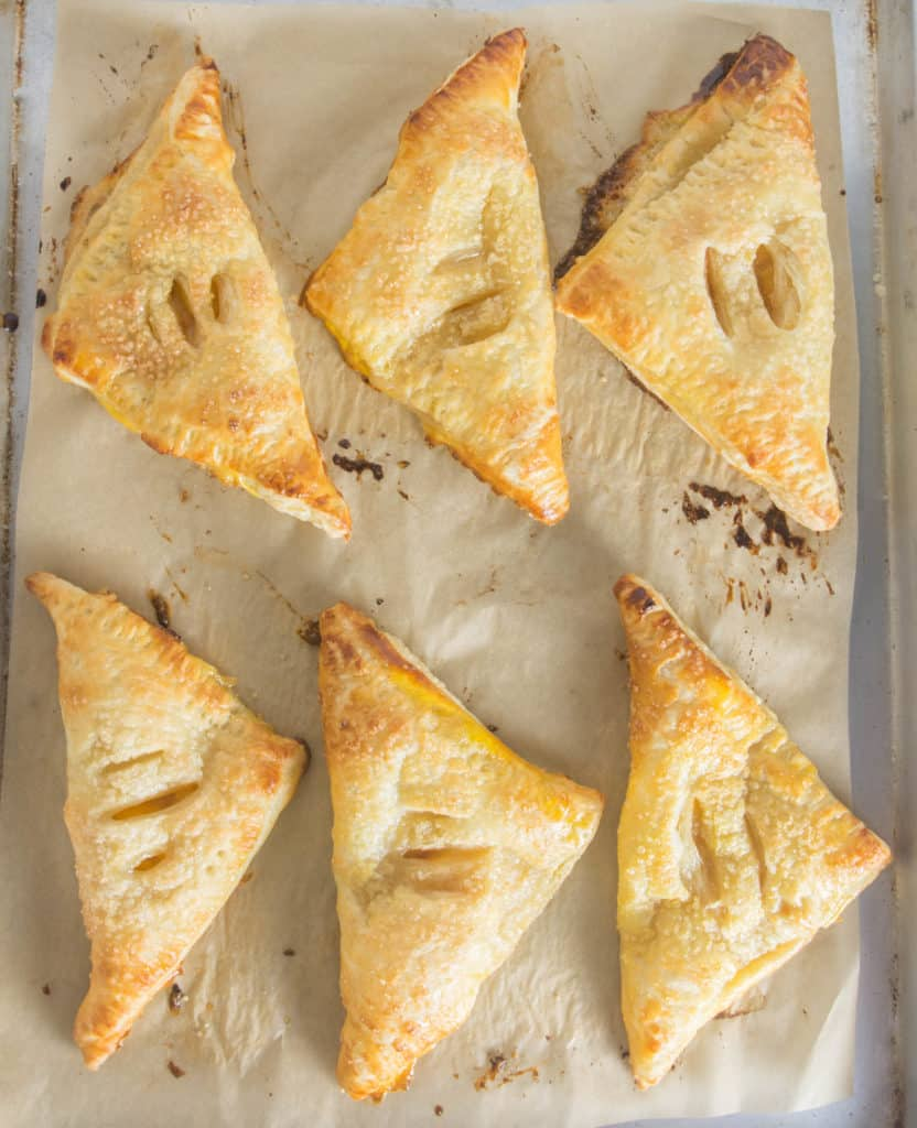 overhead shot of ginger peach turnovers on a baking sheet after they came out of the oven