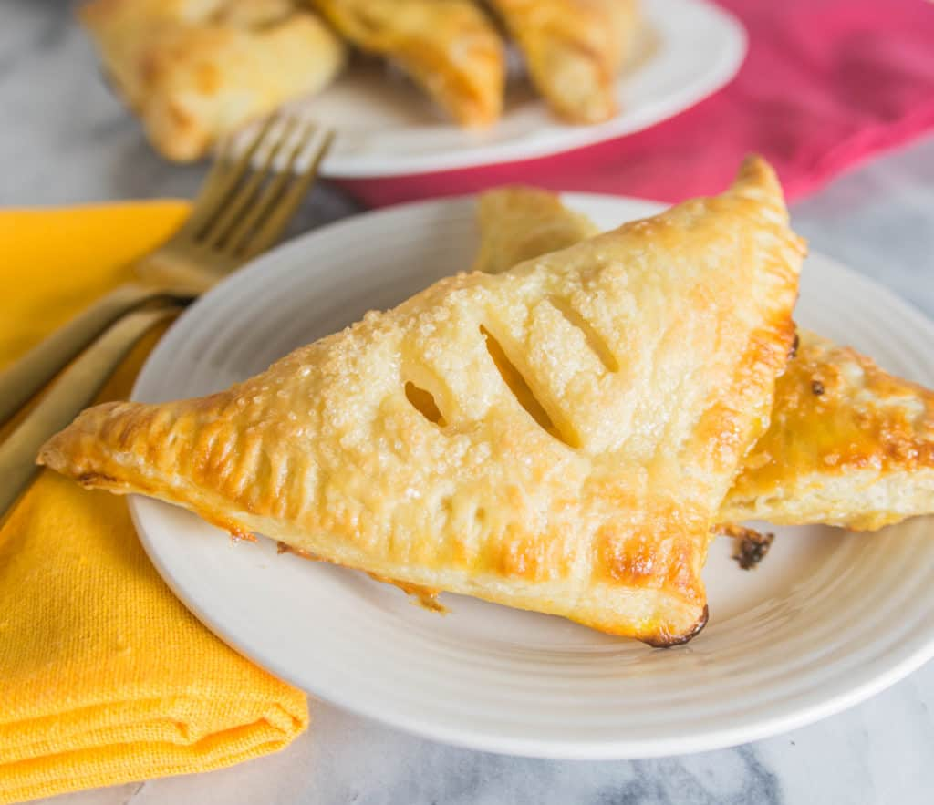 ginger peach turnovers on a plate with more turnovers on a plate in the background