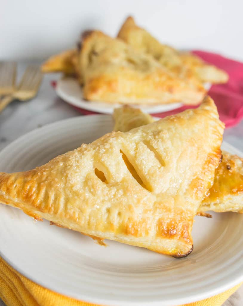 close-up photo of ginger peach turnovers on a plate with more turnovers in the background