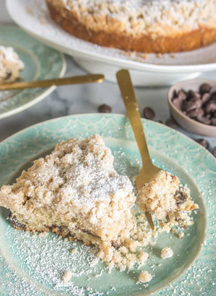 slice of chocolate chip crumb coffee cake on a plate with a fork that has taken a bite out of it