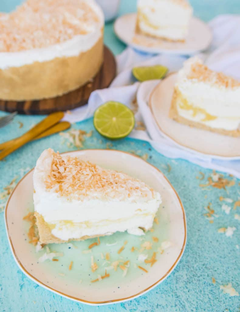 slice of coconut lime no-bake cheesecake on a plate with the rest of the cake in the background