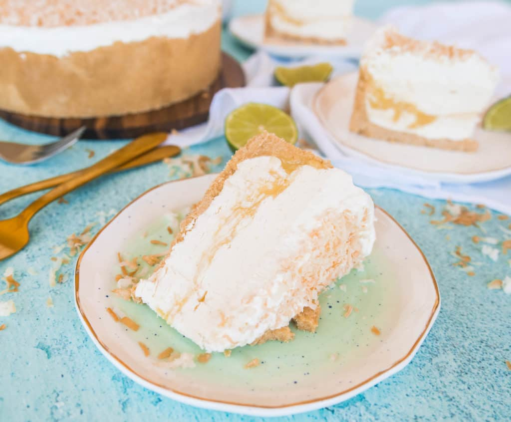 slice of coconut lime no-bake cheesecake on a plate with forks next to it and the rest of the cake in the background