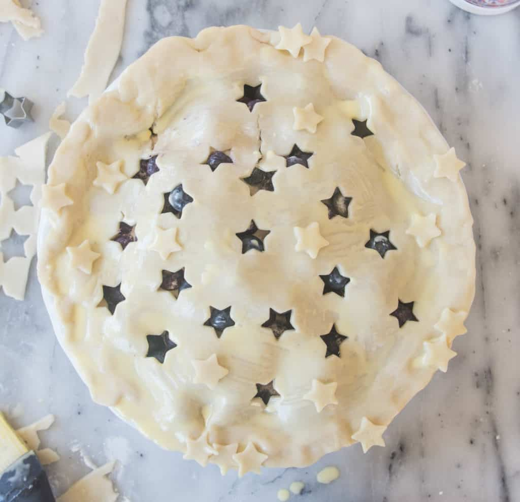 overhead shot of the unbaked blueberry pie with stars cut out of the crust