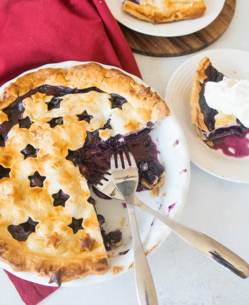 overhead shot of the sliced blueberry pie with pie on a plate to the side of the pie dish