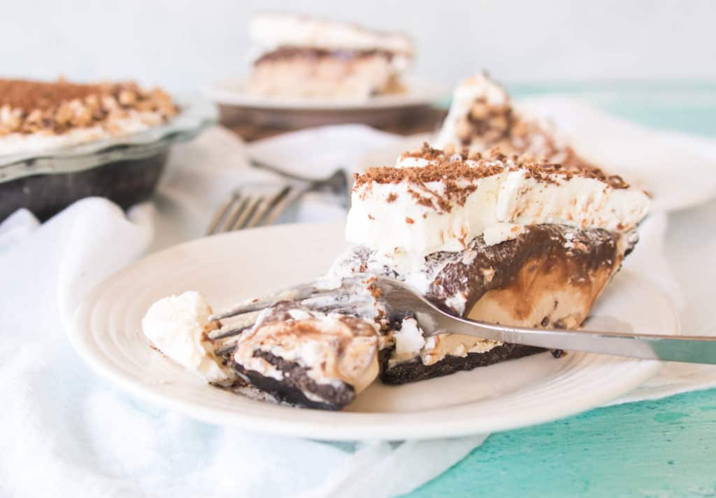slice of coffee-toffee ice cream pie on a plate with a fork taking a bite out of it