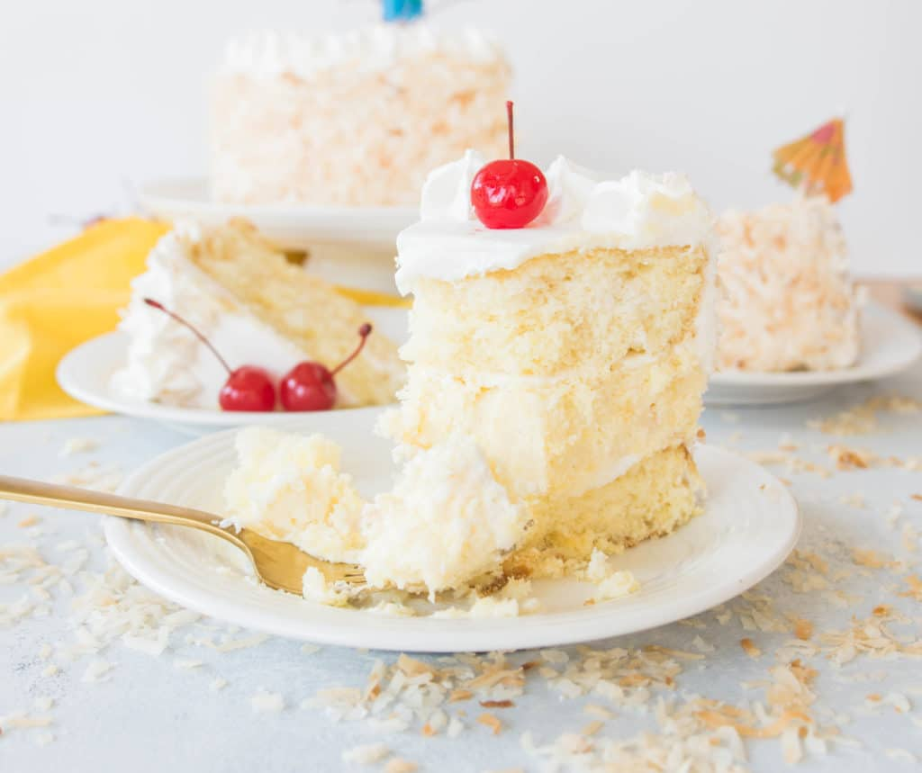 slice of piña colada cheesecake cake with a fork taking a bite out of it