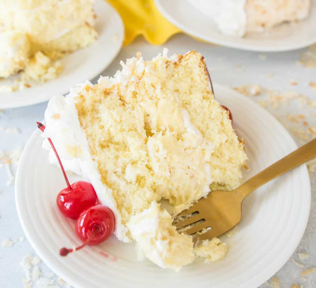 closeup photo of a slice of piña colada cheesecake cake sitting on a plate with a fork next to it