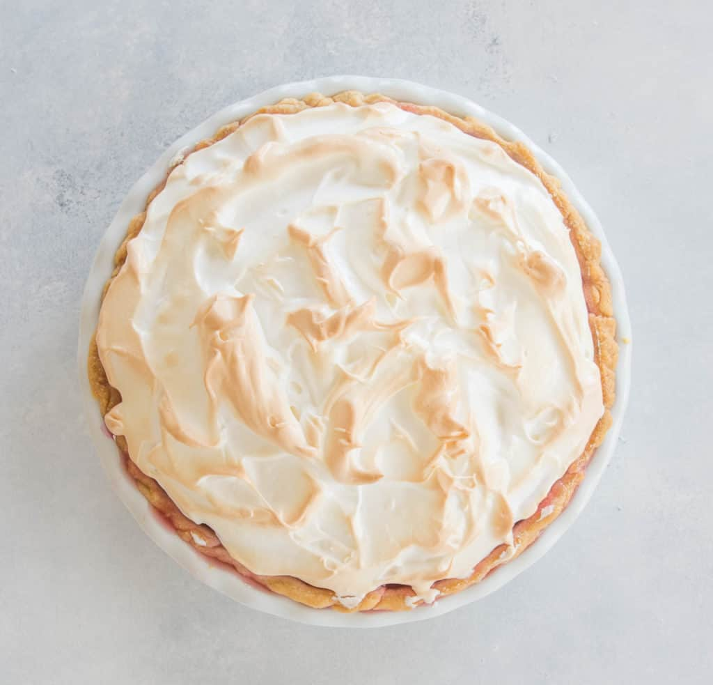 overhead photo of raspberry peach meringue pie with golden meringue