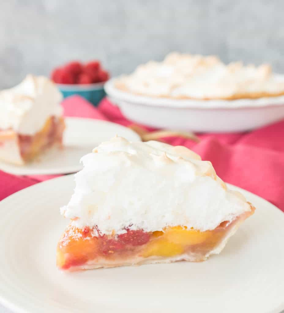 slice of raspberry peach meringue pie on a plate with the pie dish in the background