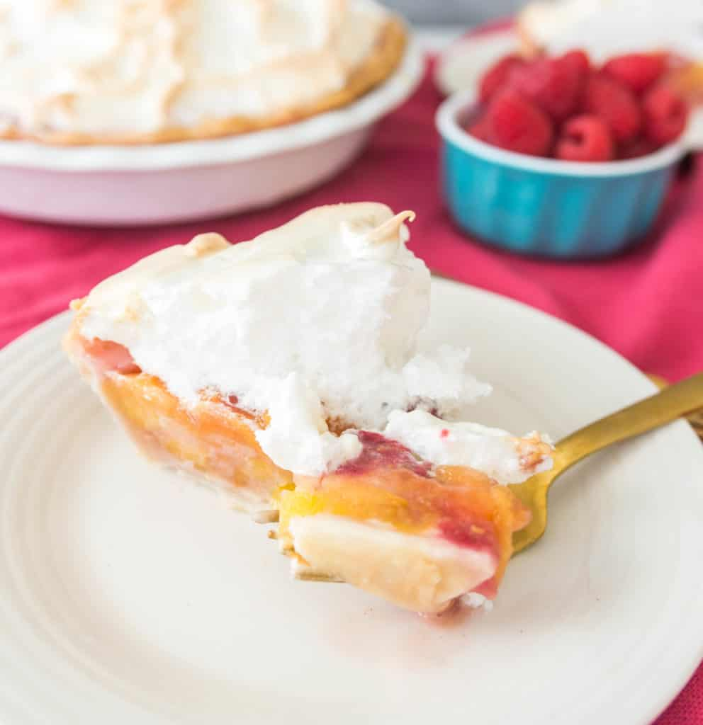 slice of raspberry peach meringue pie with a fork taking a bite out of it