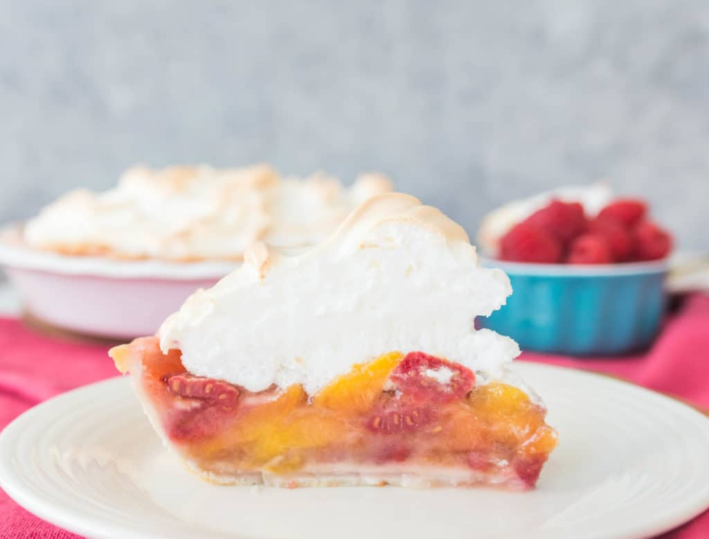 slice of raspberry peach meringue pie on a plate