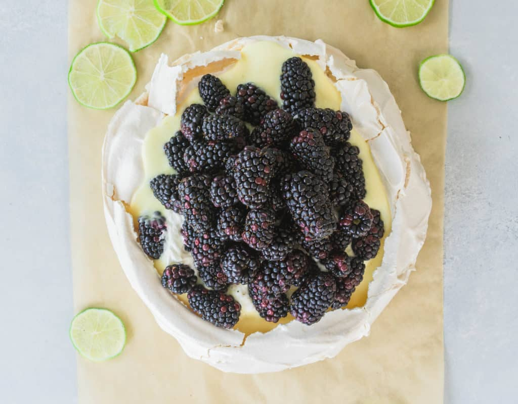 overhead photograph of completed blackberry, lime, and cardamom pavlova