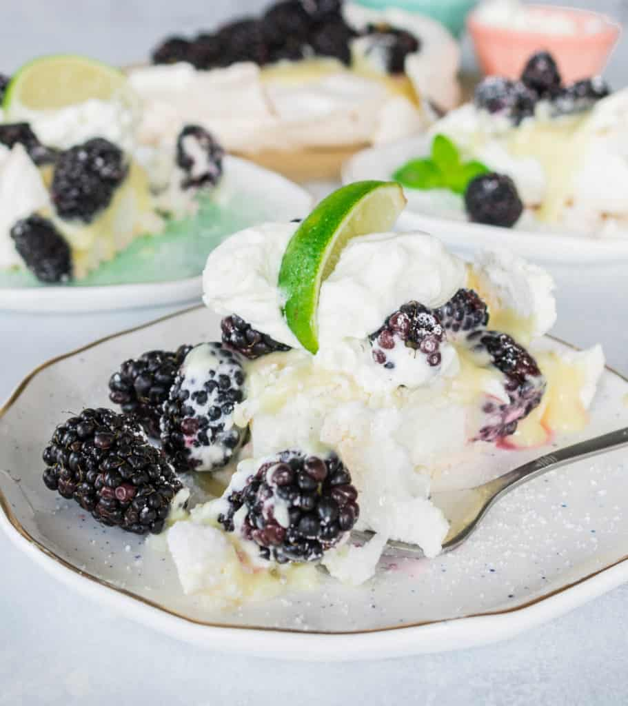 slice of blackberry, lime, and cardamom pavlova on a plate with a fork taking a bite out of it
