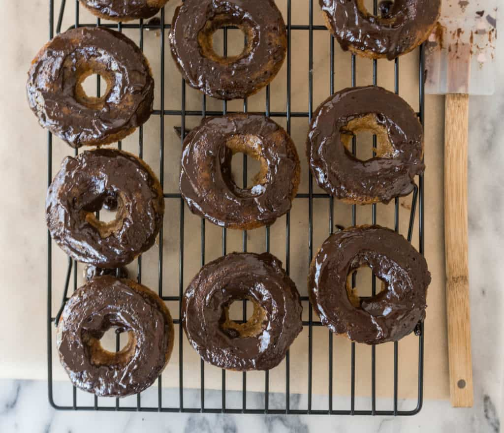 overhead shot of paleo chocolate zucchini donuts after the chocolate glaze is added