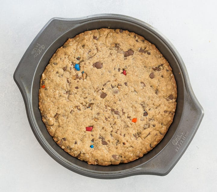 overhead photo of monster cookie cookie cake in the pan before it's been frosted
