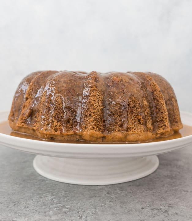 fresh apple bundt cake topped with caramel glaze sitting on a cake stand