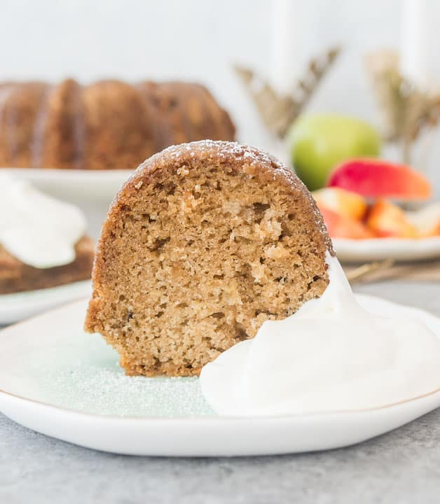 slice of fresh apple bundt cake sitting on a plate with whipped cream