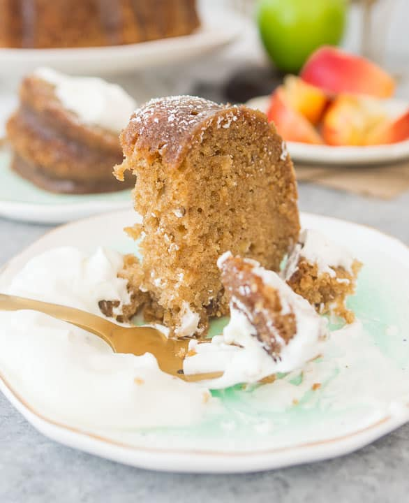 slice of fresh apple bundt cake on a plate with a fork taking a bite out of it