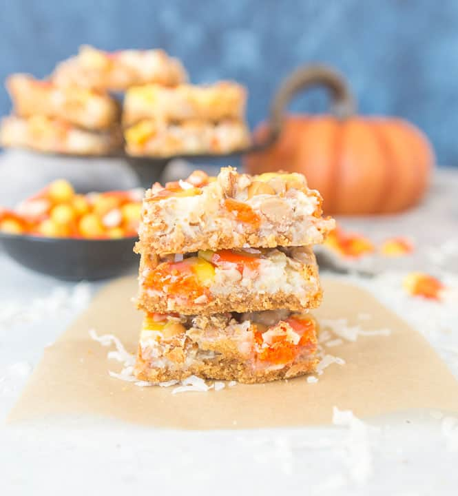 stack of butterscotch candy corn magic bars with more bars on a cupcake stand in the background