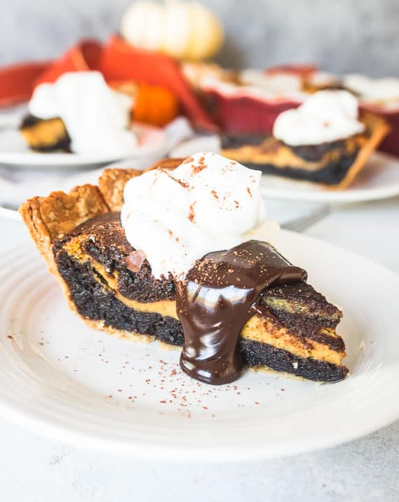 slice of pumpkin cheesecake brownie pie topped with whipped cream and hot fudge sauce
