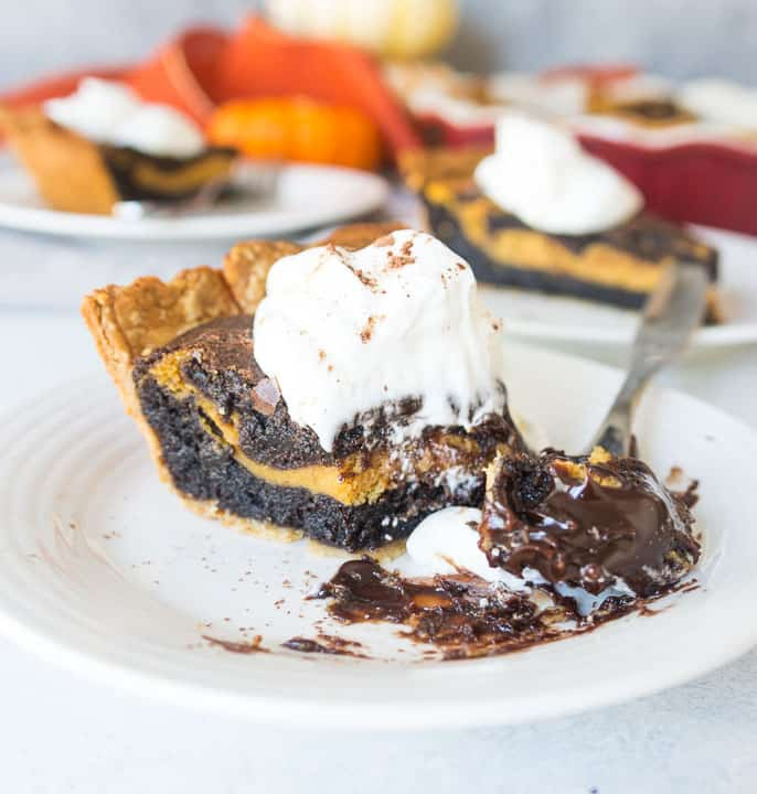 fork taking a bite out of a slice of pumpkin cheesecake brownie pie topped with whipped cream