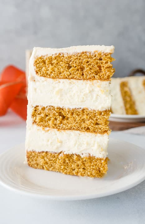 slice of pumpkin cheesecake layer cake on a plate with another slice in the background