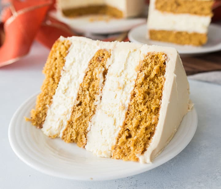 slice of pumpkin cheesecake layer cake on a plate with the rest of the cake in the background