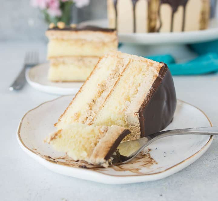 slice of white chocolate layer cake with hazelnut espresso buttercream on a plate with a fork taking a bite out of it