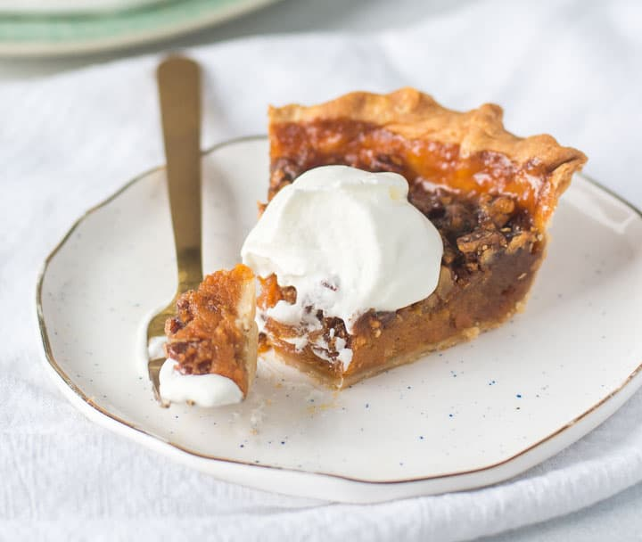 slice of sweet potato pecan pie on a plate with a fork taking a bite out of it