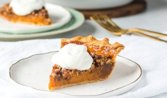 slice of sweet potato pecan pie on a plate with more pie in the background
