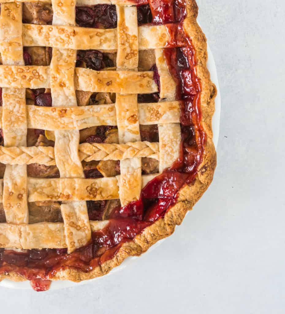 overhead view of apple cranberry pie with a lattice top crust and cranberry juices leaking out around the pie's edges