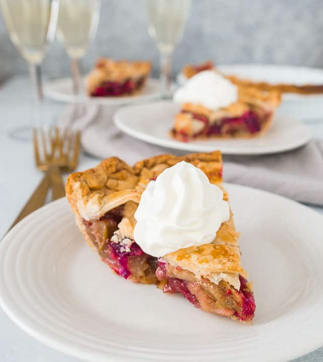 slices of apple cranberry pie on plates with three glasses of champagne in the background