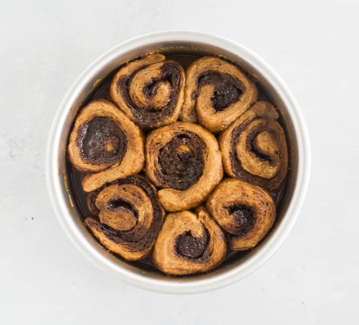 overhead photo of gingerbread cinnamon rolls in the baking dish before they've been frosted