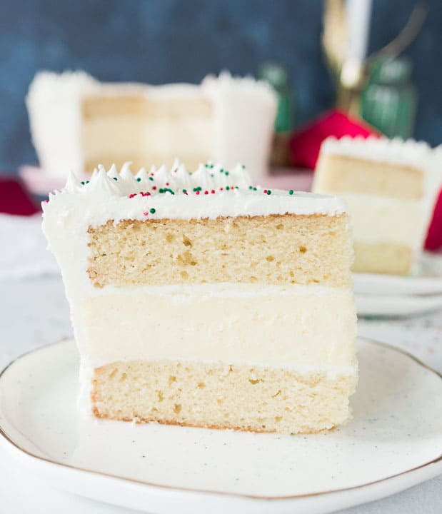 slice of white chocolate eggnog cheesecake layer cake on a plate with more cake in the background