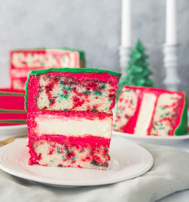 slice of Christmas funfetti cheesecake layer cake on a plate with cake and Christmas trees in the background