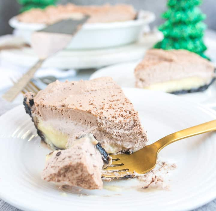 slice of chocolate eggnog cream pie with a fork taking a bite out of it