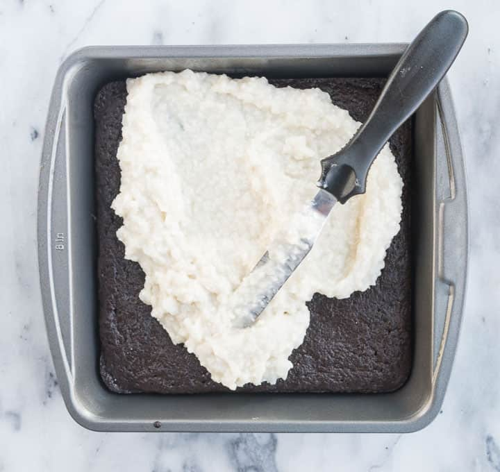 overhead photo of the paleo coconut cream brownies in a pan with a spatula spreading the topping