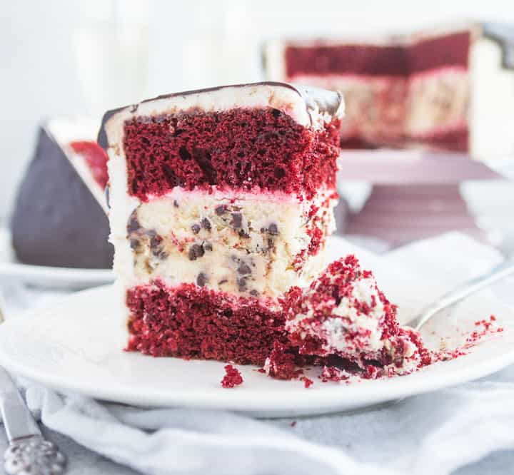 slice of red velvet cheesecake layer cake on a plate with a fork taking a bite out of it