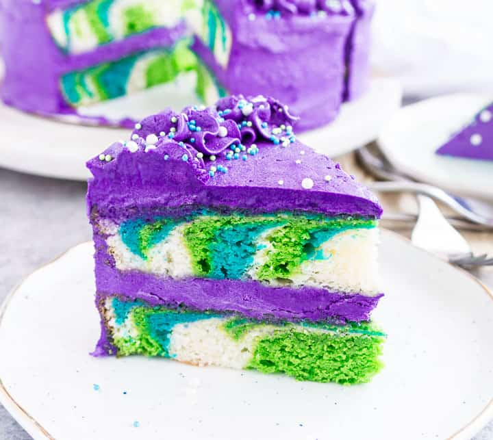 image of a slice of mermaid cake sitting on a plate with the rest of the cake in the background