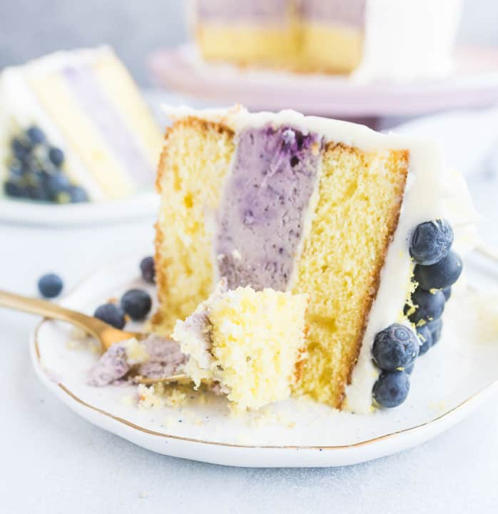 slice of lemon blueberry cheesecake layer cake sitting on a plate with a fork taking a piece out of the slice