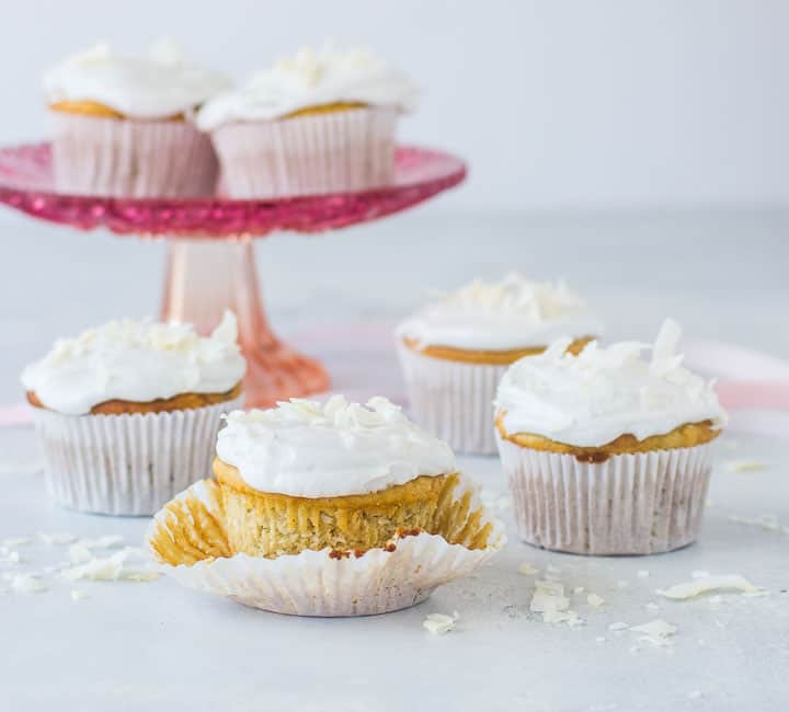 gluten-free coconut cupcakes with coconut sprinkled around them