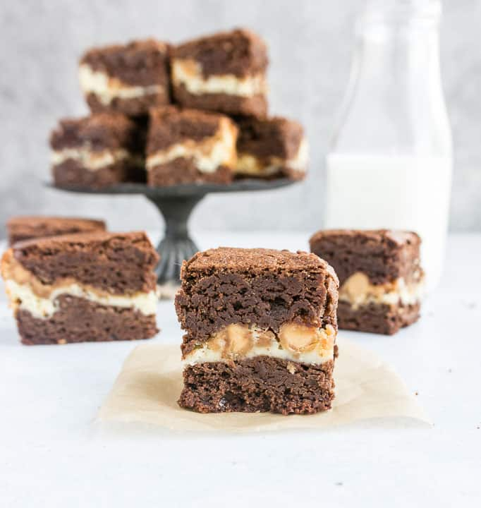 photo of a brownie sitting on a piece of parchment with more peanut butter cream cheese brownies in the background