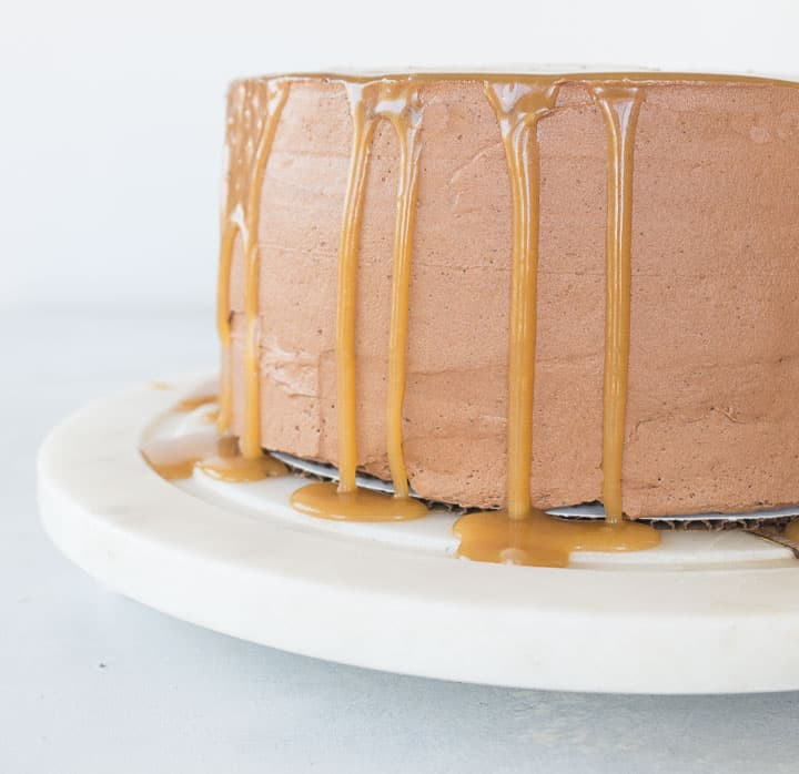 chocolate caramel cake (Milky Way cake) sitting on a cake plate with caramel dripping down the sides