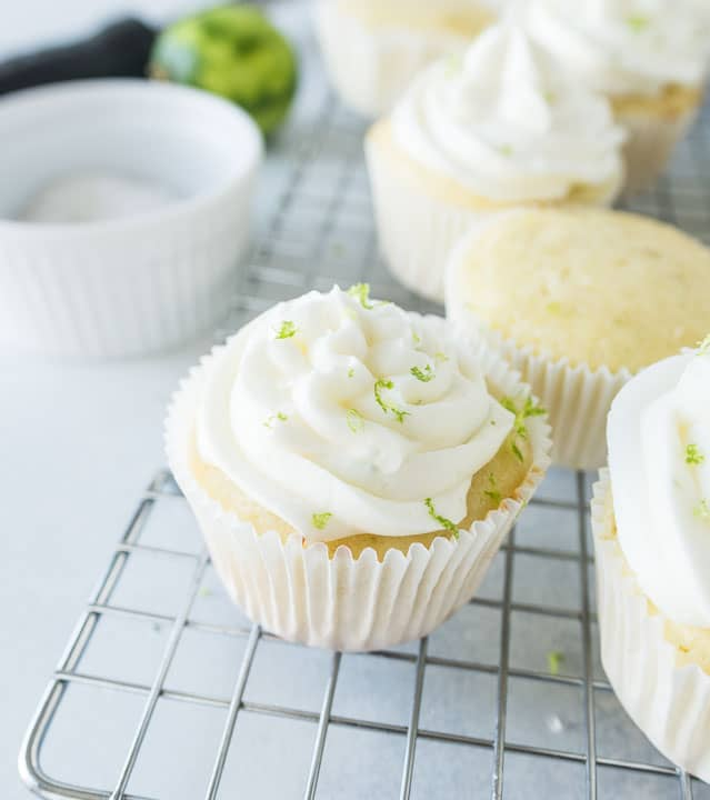 margarita cupcakes on a wire rack with salt and a lime in the background